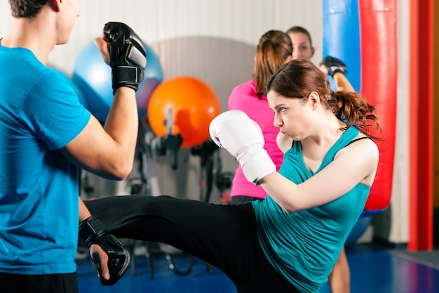 Женщины в спортзале занимаются кикбоксингом