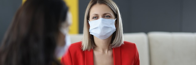 의료용 보호 마스크를 쓴 여성은 사무실에서 의사 소통합니다. 코로나 바이러스 전염병 개념의 안전한 직장