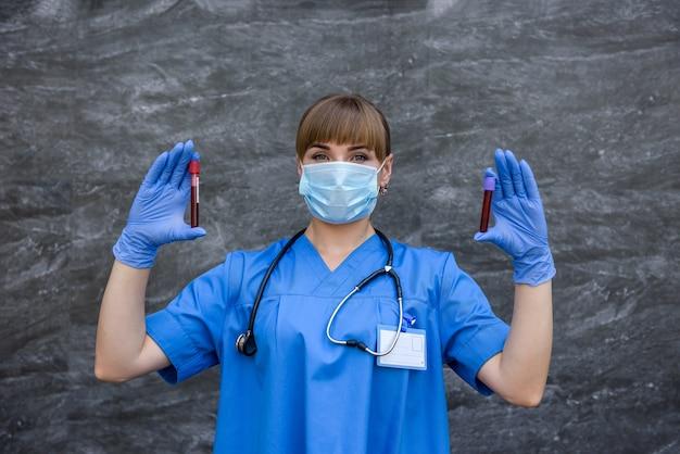 Женщины в медицинской форме позируют с пробирками с красным веществом