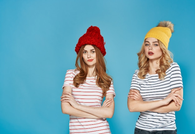 Женщины в разноцветных кепках эмоции недовольство ссора конфликт синий фон