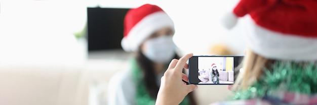 보호용 의료 마스크와 산타클로스 모자를 쓴 여성들은 휴대전화로 사진을 찍는다