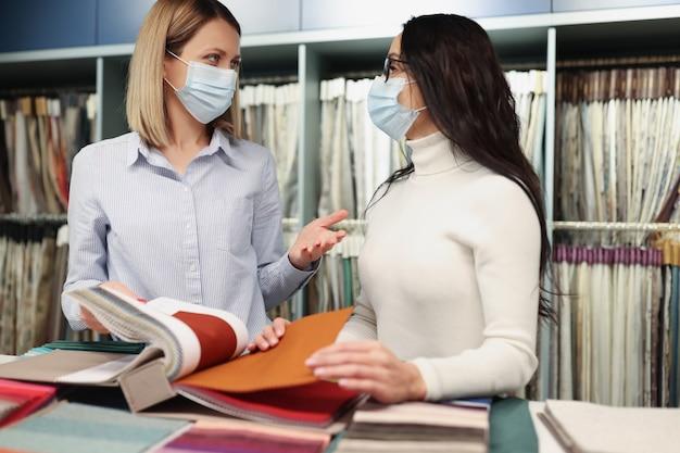 보호용 의료용 마스크를 쓴 여성들은 일하는 동안 매장에서 조직 샘플 카탈로그를 살펴봅니다.