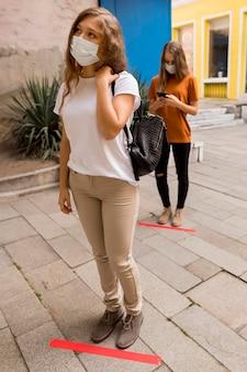 テープで屋外で列に並んでいる女性