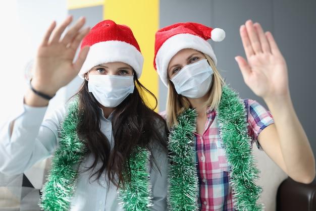 こんにちは手を振っている彼らの顔に赤いクリスマスの帽子と医療マスクの女性