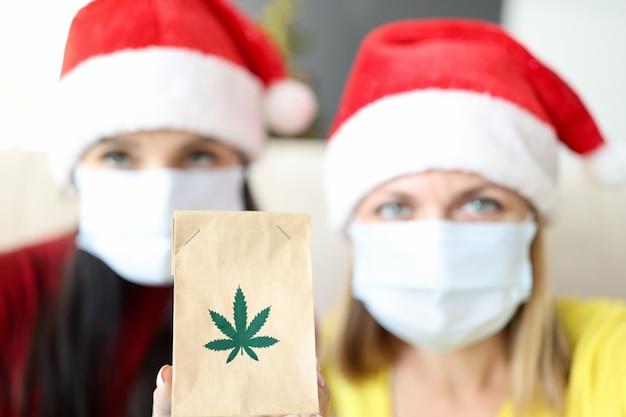 赤いサンタクロースの帽子とマリファナ抽出物と紙袋を保持している保護医療マスクの女性...
