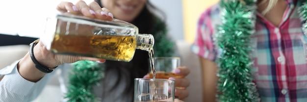 赤いサンタクロースの帽子をかぶった女性は、氷のクローズアップでガラスにアルコールを注ぐ
