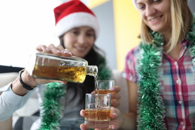 Женщины в красных шапках санта-клауса наливают алкоголь в стакан со льдом