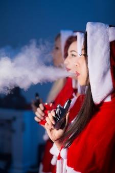 전자 담배를 피우는 산타 클로스 의상을 입은 여성