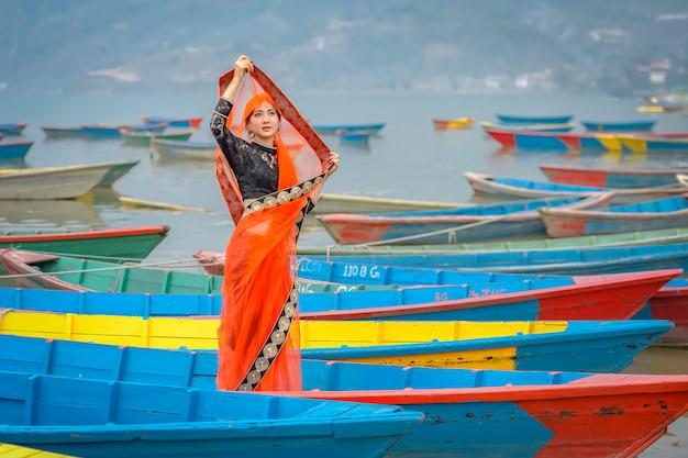 ネパール、ポカラ市、ペワ湖、ボートの上に立っているサリーの女性