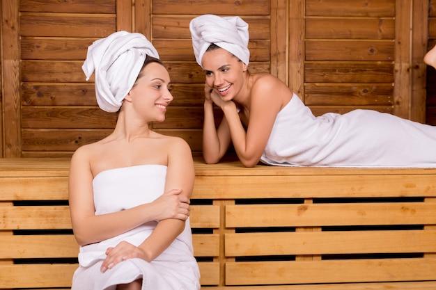 Женщины в сауне. две привлекательные женщины, завернутые в полотенце, расслабляются в сауне