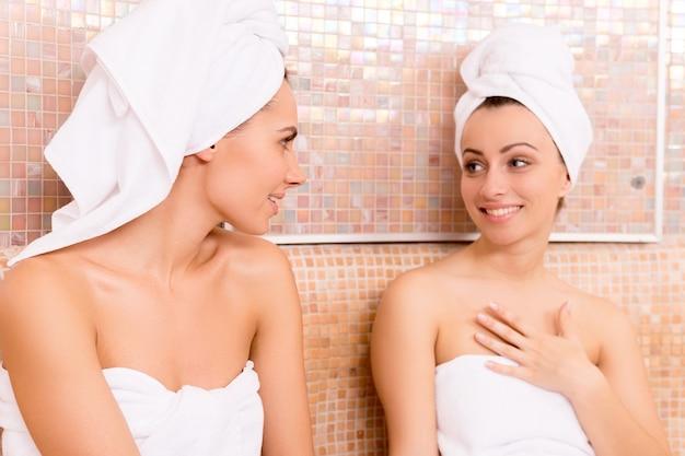 Женщины в сауне. две красивые молодые женщины, завернутые в полотенце, разговаривают друг с другом и улыбаются во время отдыха в сауне