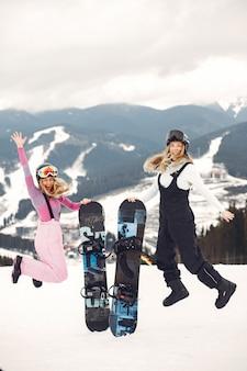 スノーボードスーツの女性。地平線上にスノーボードを手にした山のスポーツウーマン。スポーツの概念