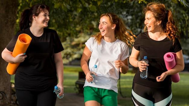 Женщины в спортивной одежде болтают на открытом воздухе