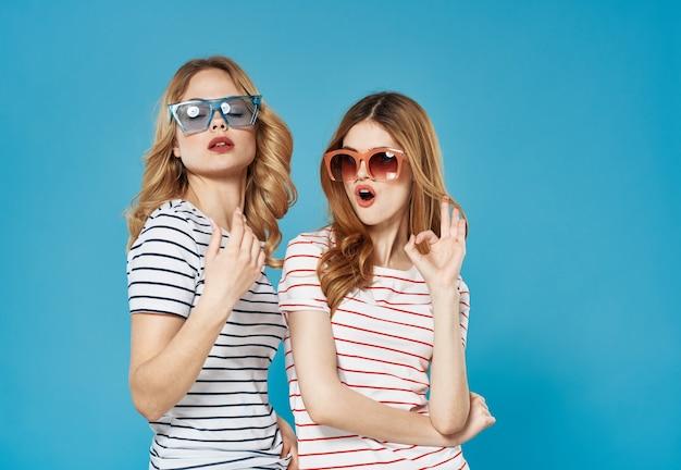 ストライプのtシャツサングラスの女性は感情の青い背景を喜びます。高品質の写真