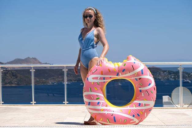 リゾートのプールの近くのサングラスの膨脹可能なドーナツの女性