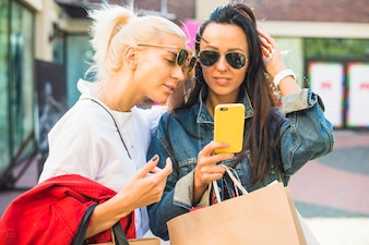 Women in sunglasses looking at smartphone