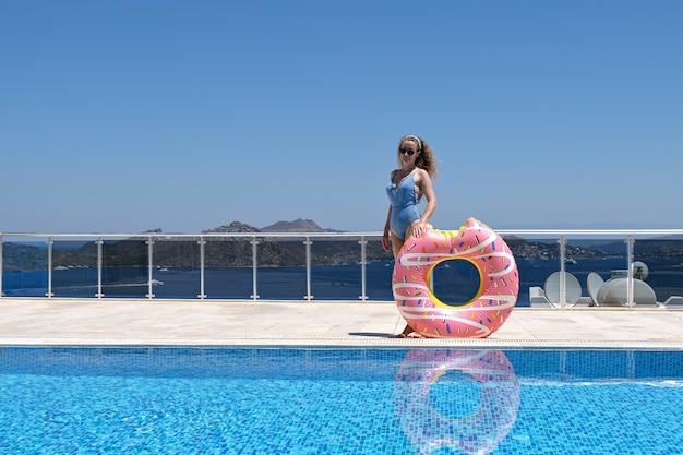 리조트 수영장 근처 풍선 도넛과 함께 포즈를 취하는 선글라스에 여성.