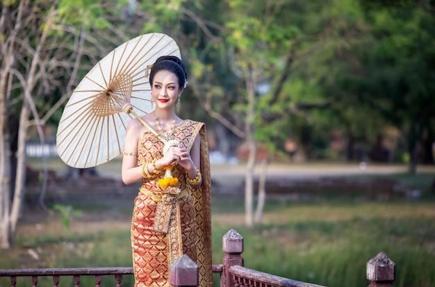 傘を保持しているタイの伝統的な衣装の女性