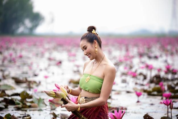 蓮の湖に立つタイの伝統的な衣装の女性
