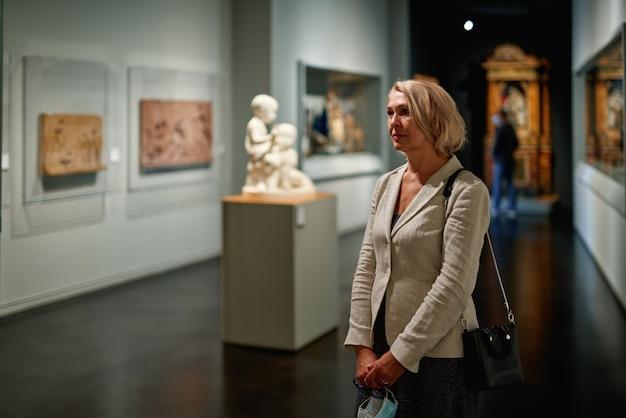 美術館の女性が美術展を見る