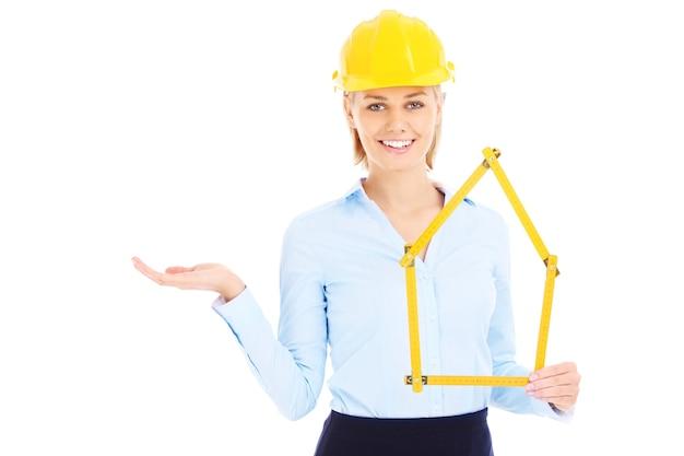 空白のスペースを提示する黄色いヘルメットの女性