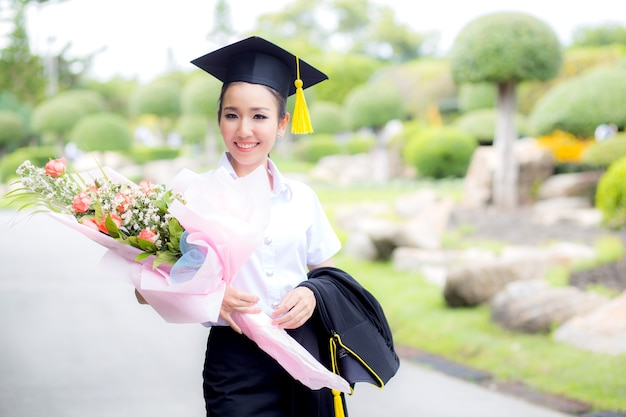女性は、花束を保持し、カメラのために笑顔大学院です。