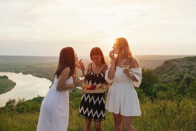 女性は屋外でピクニックをしています。彼らは新鮮な果物を食べ、ワインを飲み、川を背景にした丘で週末を楽しんでいます。