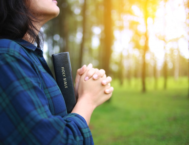 女性は自然の中で神に祈ります。