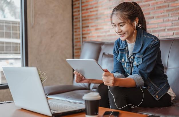女性はコーヒーショップで働いた後のコーヒー休憩中にラボトップで見たり買い物したりするのにリラックスしています Premium写真