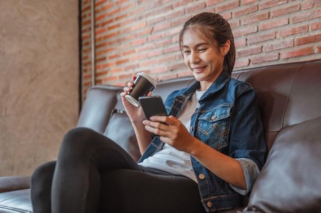 女性はコーヒーショップで働いた後のコーヒー休憩中にラボトップで見たり買い物したりするのにリラックスしています
