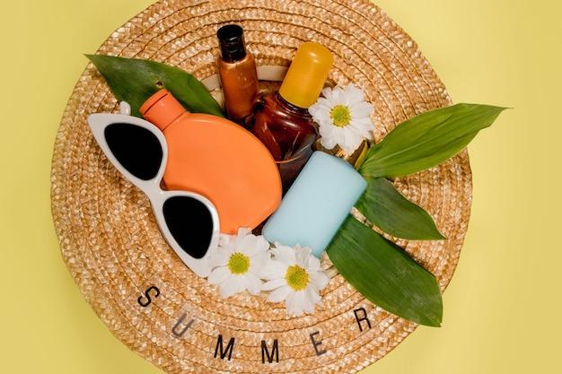女性は、色付きの背景のトップ ビューにビーチ アクセサリーと夏の麦わら帽子です。