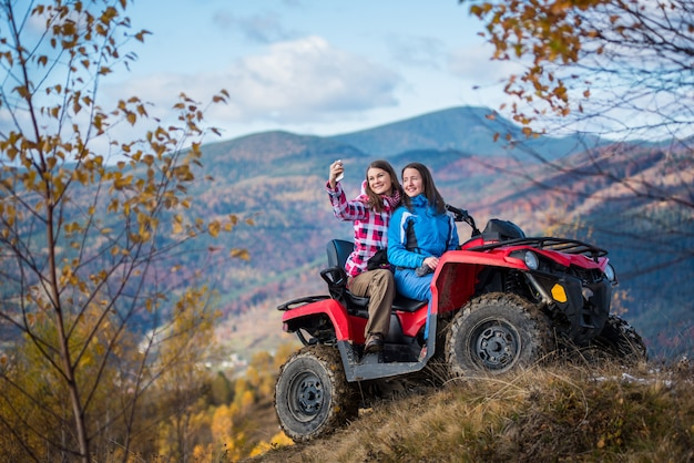 Women in jackets on red atv at the hill makes selfie on the phone