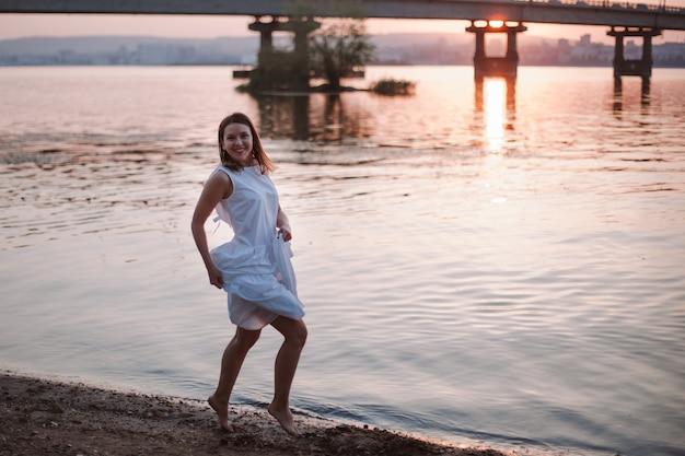 Женщины прыгают на закате смеющаяся жизнерадостная женщина в белом летнем платье развлекается на т ...