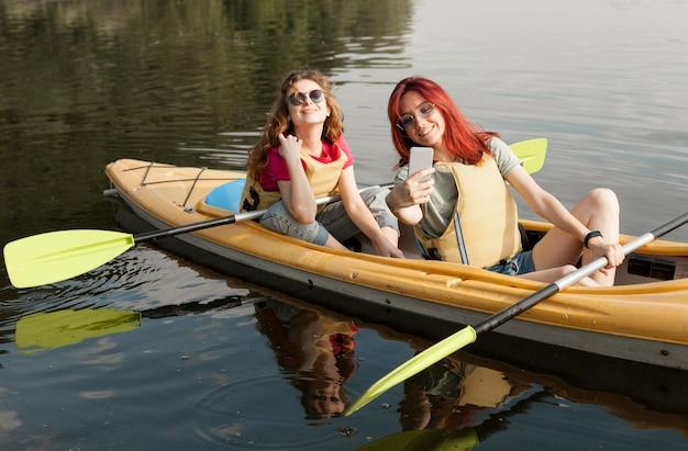 Women in kayak taking selfie