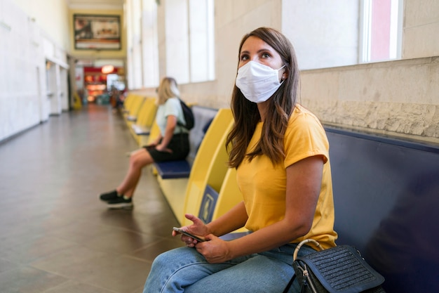 Donne che mantengono una distanza sociale alla stazione dei trasporti pubblici