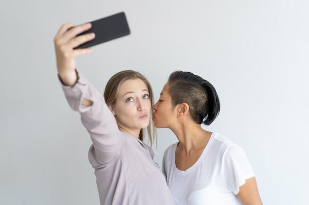 Женщины целуются и делают селфи фото