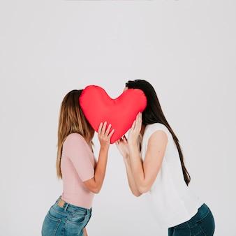 Donne che si baciano dietro il cuore