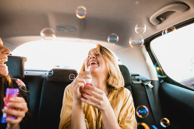 Women laughing and blowing bubbles in car
