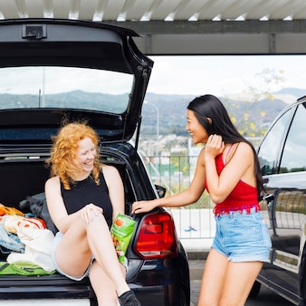 Women laughing and having fun by car trunk