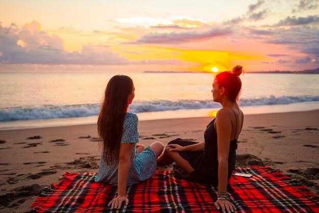 Женщины лежат на пляже, наслаждаясь летними каникулами, глядя на море