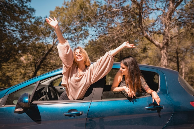 Women leaning out of car windows
