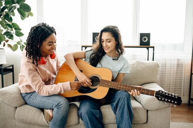 女性は家でギターを弾くことを学びます。イヤホンをしたかわいいガールフレンドが部屋でくつろぎ、音の愛好家がソファで休んで、女性の友達が一緒にレジャーをする