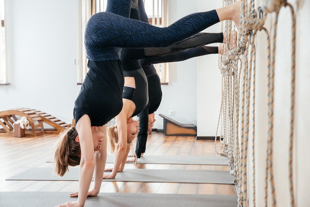 Women learning to stand on hands near wall in studio. upside down yoga position