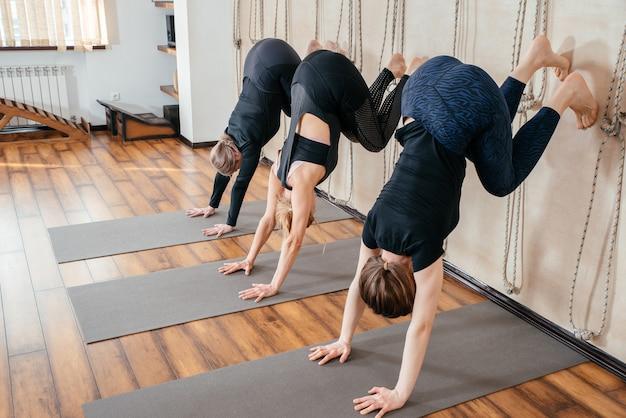 Женщины учатся стоять на руках у стены в студии. поза для йоги вверх ногами
