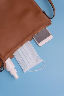 マスク、ハンドジェル、携帯電話付きの女性用レザーバッグは、covid-19から保護します。コロナウイルス、トップビュー