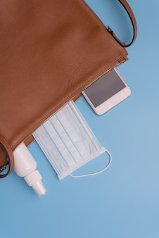 Women leather bag with masks, hand gel and mobile phone  protect from covid-19. coronavirus,top view