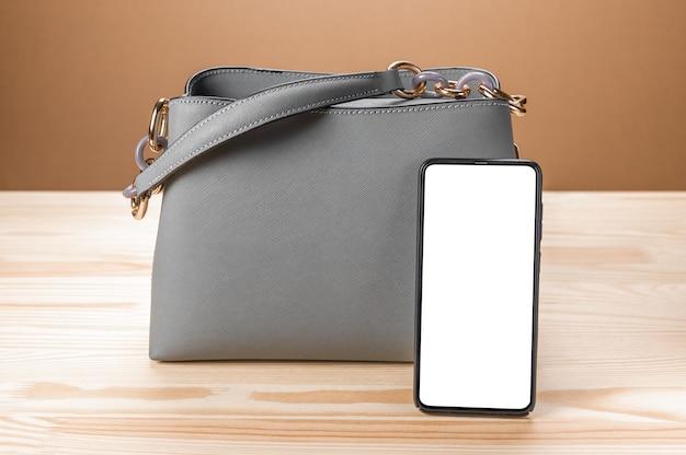 여자 가죽 회색 핸드백과 빈 흰색 화면이있는 셀 모바일 스마트 폰.