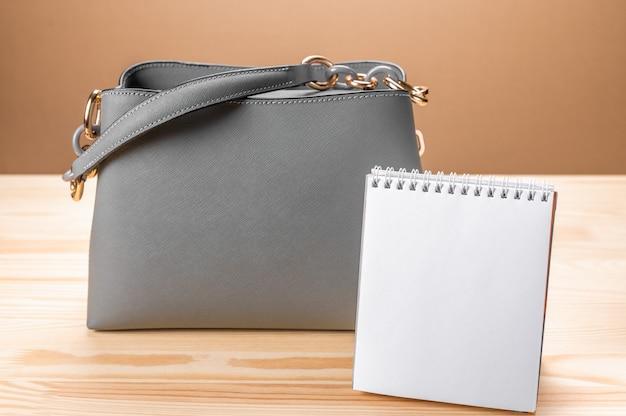 여성 가죽 회색 핸드백과 메모장. 여성용 가방 및 메모장 쓰기.