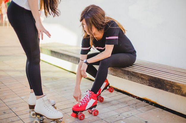 Women in leggings and shirt touching rollerskates