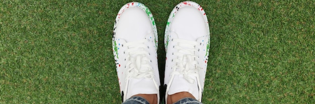 Women legs in blue jeans and white beautiful sneakers on green lawn